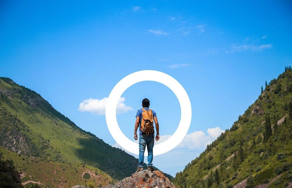Un chico en la cima de una montaña, listo para su próximo reto, con ayuda y subvenciones de Aming