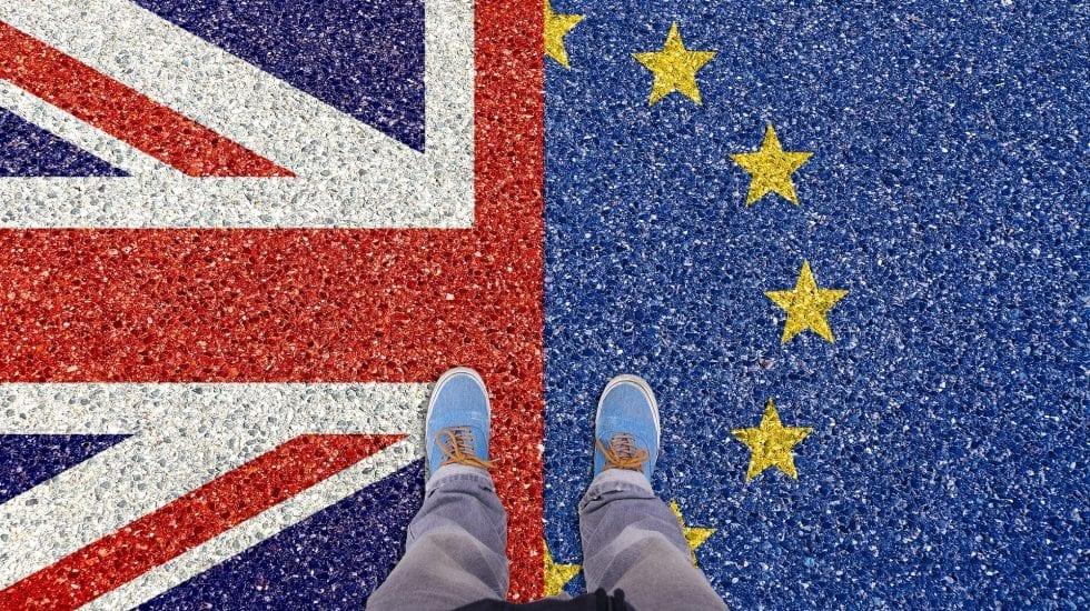 Consecuencias de un Brexit duro, unos pies pisan una alfombra en la que la mitad es la bandera de UK y la otra mitad la de la UE.