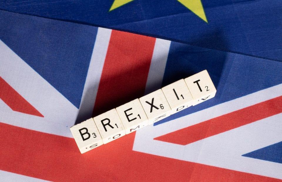 """consecuencias fiscales de un brexit duro. Banderas de Unión Europea y Reino Unido superpuestas. Encima unos dados en los que está la palabra """"BREXIT""""."""