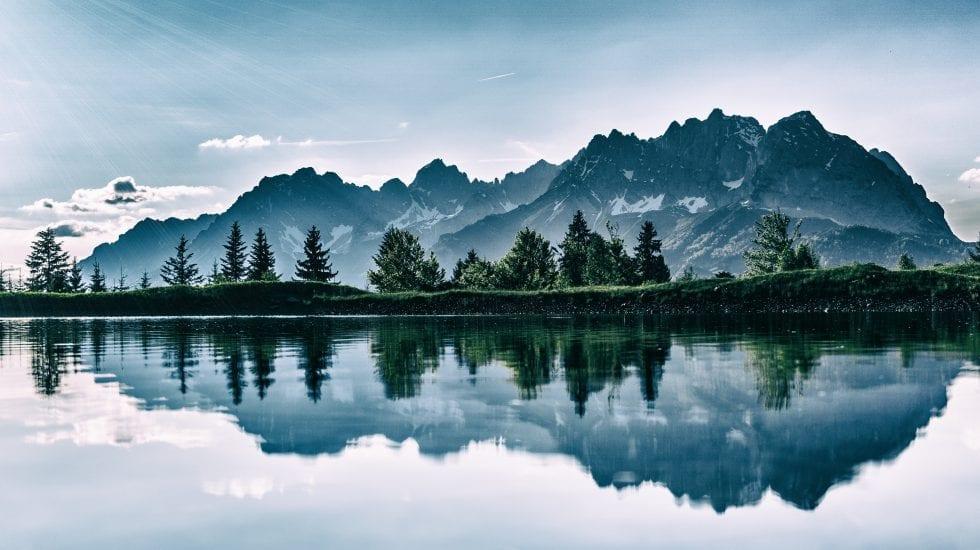 Paisaje de montañas y su reflejo en un lago creando simetría horizontal. Compra pública de innovación