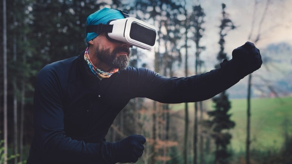 Hombre con gafas de Realidad Aumentada en medio de un bosque