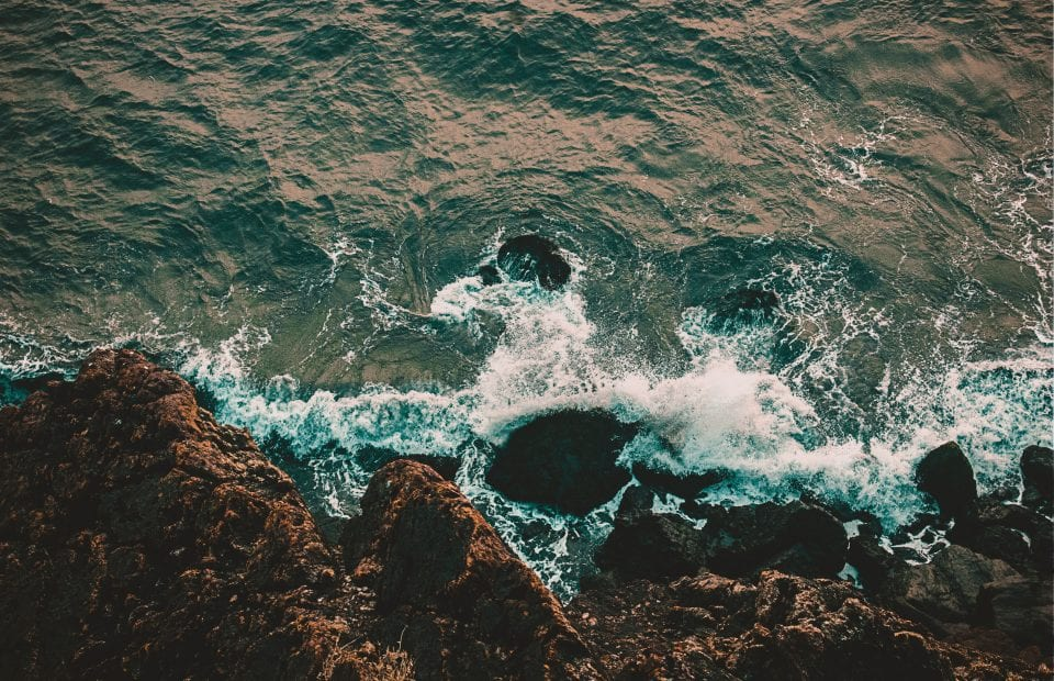 Ayuda mar menor, vista cenital del mar chocando con unas rocas