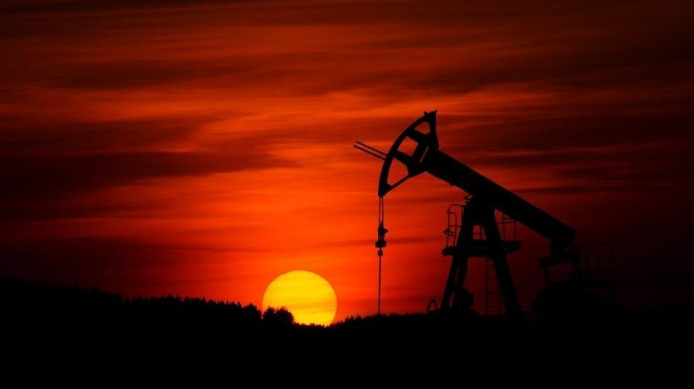 atardecer con la silueta de una bomba en una explotación petrolífera. Mercado energético.